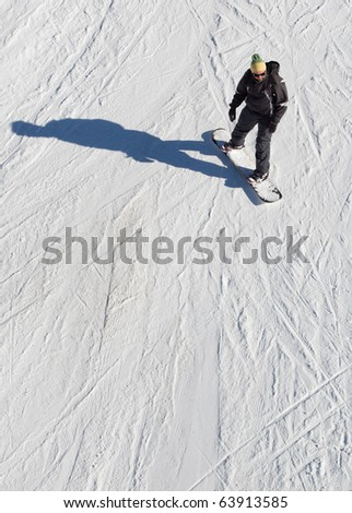 Snowboarder from above on a snow slope riding his snowboard. - stock photo