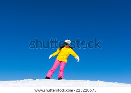 snowboarder girl making stunt trick on snowboard, snow mountain slope copy space blue sky