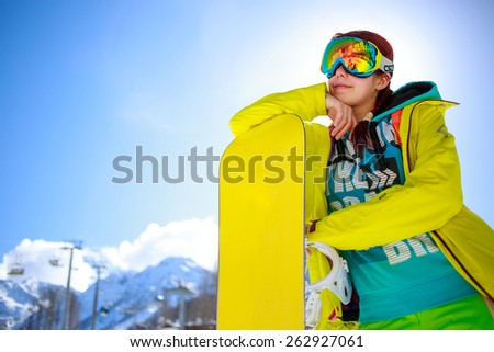 snowboarder girl standing hold snowboard against blue sky - stock photo