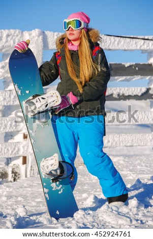 Snowboarder girl stands with snowboard. Sheregesh resort, Siberia, Russia - stock photo