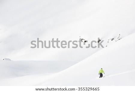 Snowboarder goes downhill in fresh powder snow in a winter mountain landscape. Italian Alps, Europe. - stock photo