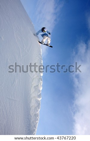 snowboarder goes downwards on a steep wall - stock photo