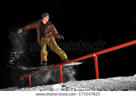 Snowboarder grinding the Rail