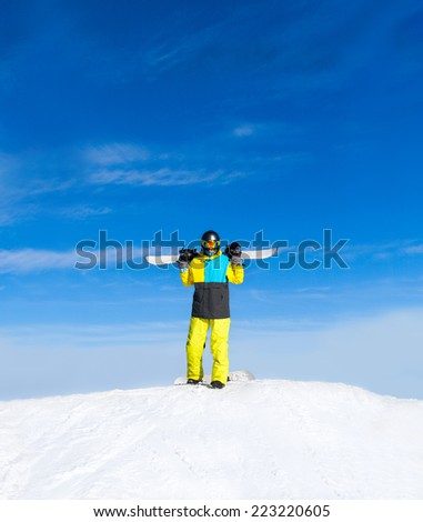 Snowboarder hold snowboard on top of hill, snow mountains snowboarding on slopes - stock photo