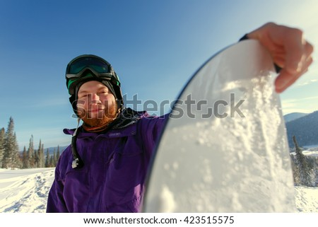 Snowboarder holds snowboard on top of hill, close up portrait - stock photo