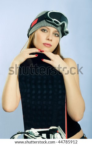 Snowboarder in a goggles holding her board - stock photo