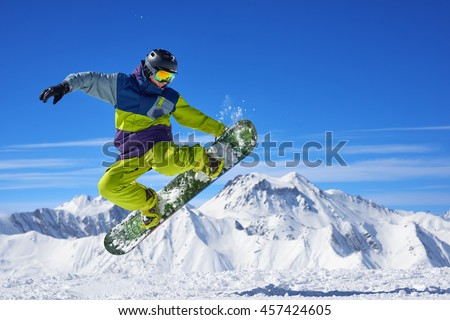 Snowboarder in bright sportswear doing trick against of beautiful mountains