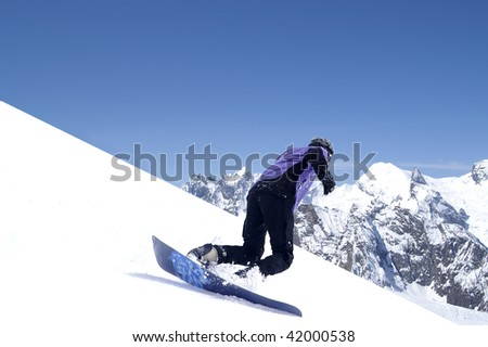 Snowboarder in Caucasus Mountains. Winter resort Dombaj. - stock photo