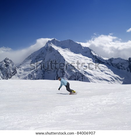 Snowboarder in high mountains. Caucasus, Dombay