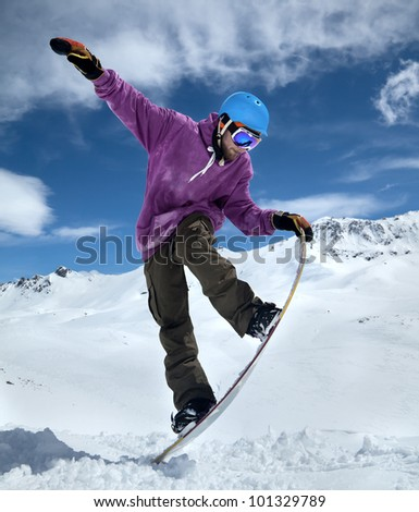Snowboarder in mountains taking for the edge snowboard against the blue sky and clouds - stock photo