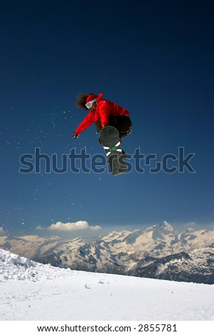 Snowboarder in red jacket jumping high - winter mountains action scene