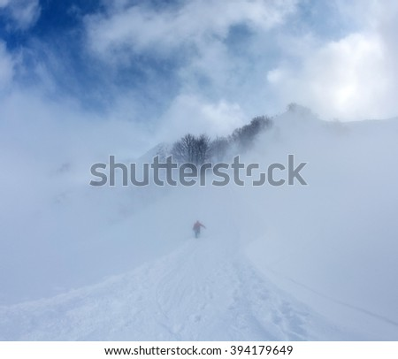 Snowboarder in the mist rises on the mountainside along the road up on background blue sky and clouds - stock photo