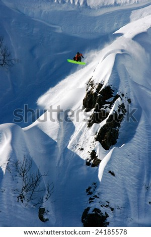 Snowboarder jump from big rock - stock photo