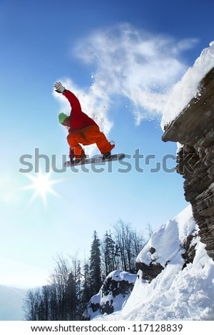 Snowboarder jumping against blue sky - stock photo
