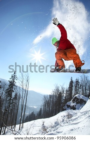Snowboarder jumping against blue sky  and sun rays - stock photo