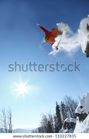 Snowboarder jumping against blue sky from the snow  cliff - stock photo