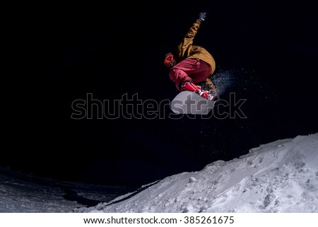 Snowboarder jumping at night.