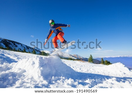Snowboarder jumping high from hill in winter