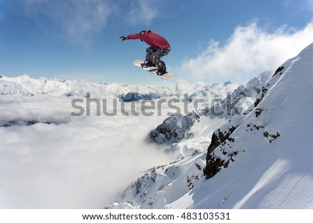 Snowboarder jumping in snowy winter mountains
