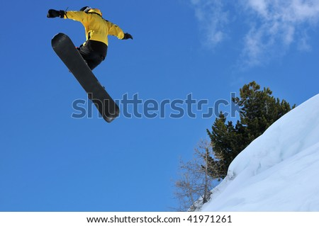 snowboarder jumping off a ridge of snow