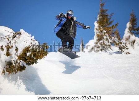 Snowboarder jumping on mountain slope - stock photo