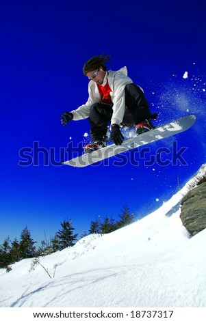 snowboarder jumping over the rock