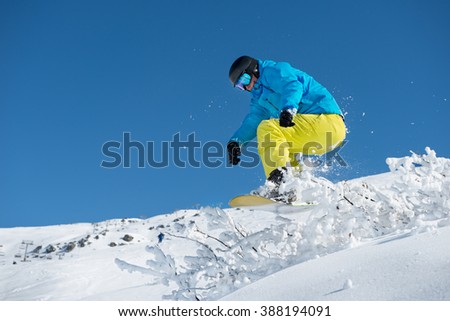 Snowboarder jumping over the snowy shrub while off-piste  riding  - stock photo