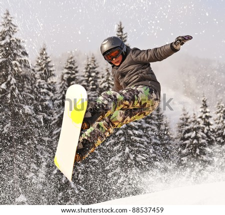 Snowboarder jumping through - stock photo