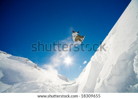 Snowboarder jumping through air with blue sky in background - stock photo