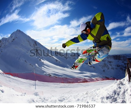 Snowboarder jumping through air with deep blue sky and clouds in background - stock photo