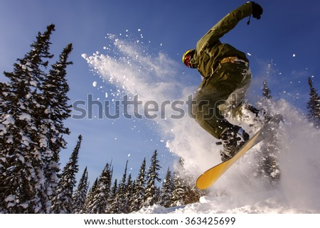 Snowboarder jumping through air with sky in background - stock photo