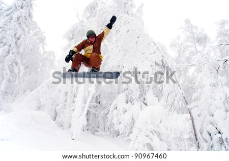 Snowboarder jumping through air with white forest in background - stock photo
