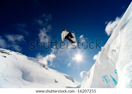 Snowboarder jumping through the air with blue sky background - stock photo