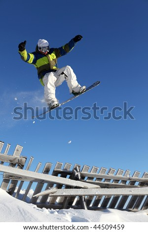 snowboarder jumps through for a pine forest against the sky - stock photo