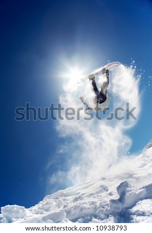 Snowboarder launching off a jump; La Thuile , Aosta, Italy. - stock photo