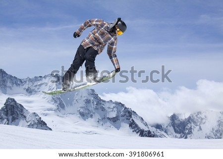Snowboarder making jump, extreme mountain freeride.