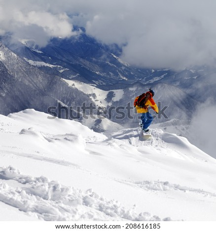 Snowboarder on off-piste slope an mountains in haze. Caucasus Mountains, Georgia. - stock photo