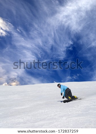 Snowboarder on off-piste slope and sky with clouds - stock photo