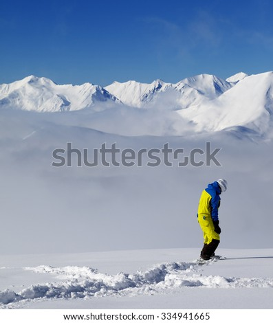 Snowboarder on off-piste slope with new fallen snow. Caucasus Mountains, Georgia. Ski resort Gudauri. - stock photo