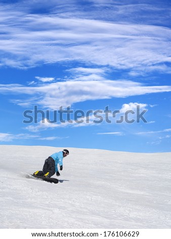 Snowboarder on ski slope and blue sky with clouds at nice sun day - stock photo
