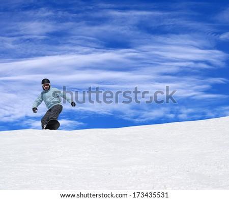 Snowboarder on ski slope at nice sun day - stock photo