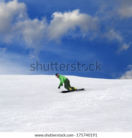 Snowboarder on ski slope at nice sun day - stock photo