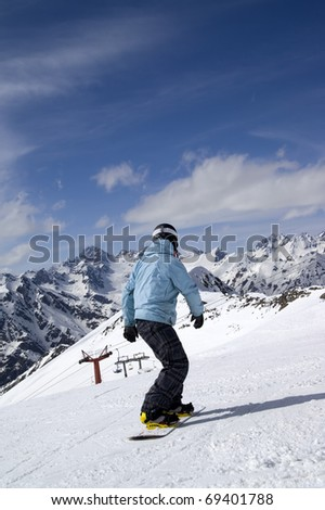 Snowboarder on ski slope. Ski resort Dombay, Caucasus Mountains.