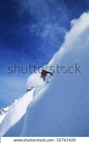 Snowboarder on steep slope - stock photo