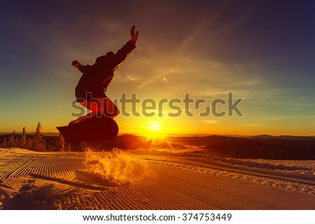 Snowboarder on the mountain with a sunset in the background - stock photo