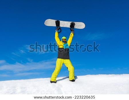 Snowboarder raised hands arms up hold snowboard on top of hill, snow mountains snowboarding on slopes