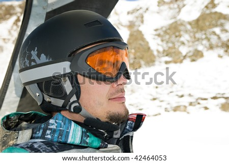 Snowboarder riding a chairlift. Profile head shot