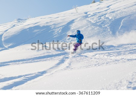 Snowboarder riding fresh snow powder in mountains.