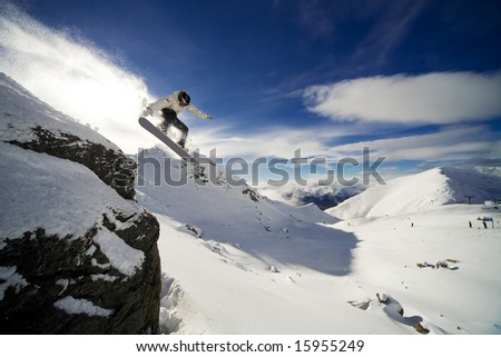 Snowboarder riding off cliff with deep blue sky in background - stock photo