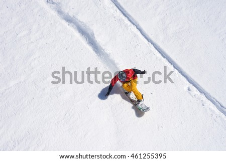 Snowboarder riding on loose snow Freeride top view.